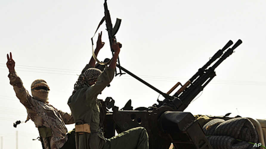 Anti-Gadhafi fighters with weapons move to the front line, 90 km east of Sirte, from Om El Qandil, 90 km west of Ras Lanuf September 6, 2011.