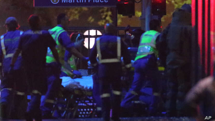 FILE - Armed tactical response officers and emergency workers attend the scene after a cafe siege in the central business district of Sydney , Australia.