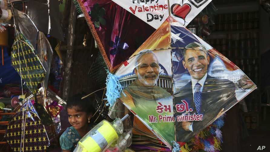 An Indian girl stands near a kite with portraits of India's Prime Minister Narendra Modi and U.S. President Barack Obama, displayed for sale at a shop ahead of the Hindu festival of Makar Sakranti, also knowns as kite festival, in Hyderabad, India, M