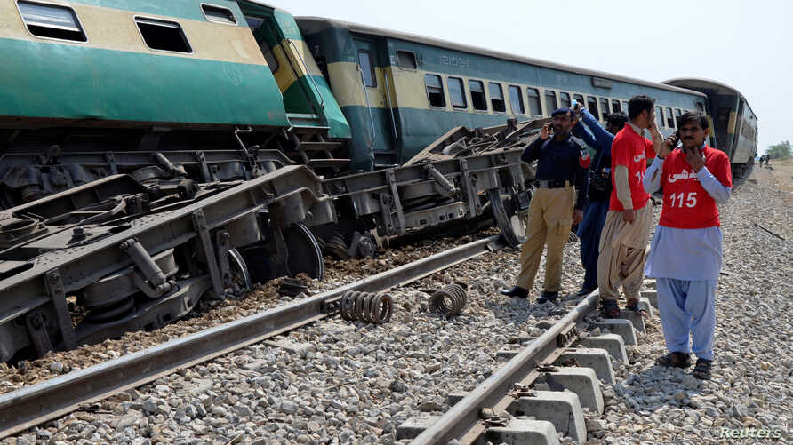 A police officer and rescue workers stand near to a derailed passenger train, after a bomb went off on track in Naseerabad, Pakistan, March 17, 2019.