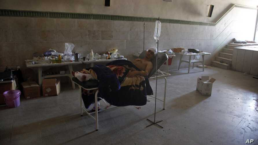 Mahmoud, 21, a Palestinian resident of Syria, rests in a field hospital after he was found Monday, August 6, 2012, with three gunshot wounds in the town of Anadan on the outskirts of Aleppo, Syria.