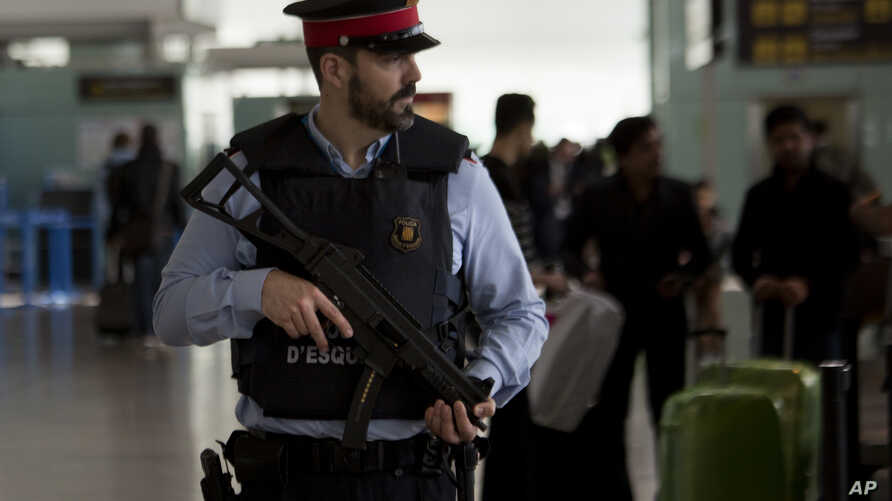 FILE - A police officer guards a terminal of the airport during tighter security measures  in Barcelona, Spain.