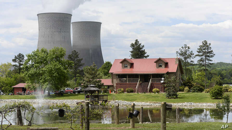 FILE- A home sits within view of the Watts Bar Nuclear Plant cooling towers Unit 1 (L) and Unit 2 near Spring City, Tenn.