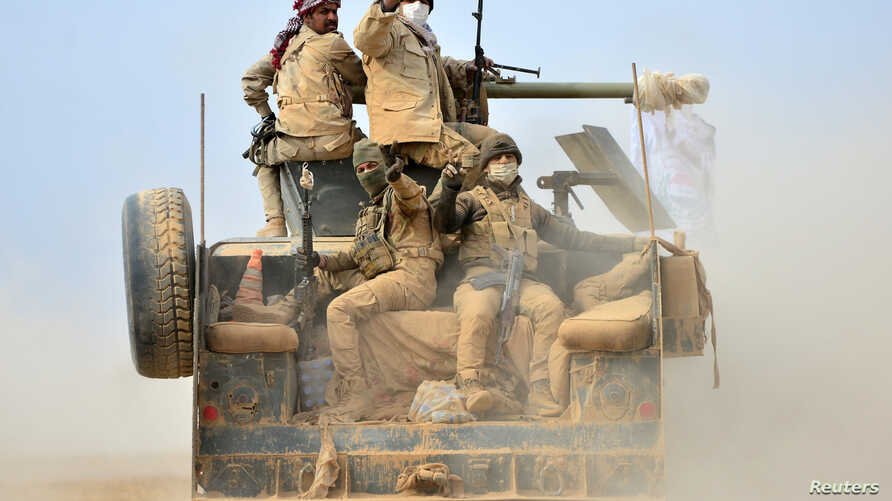 Shi'ite fighters ride on a military vehicle heading toward the airport of Tal Afar during a battle with Islamic State militants in Tal Afar, Iraq, Nov. 16, 2016.