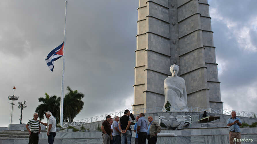 Cuban flag flies at half mast at Revolution Square as people gather following the announcement of the death of Cuban revolutionary leader Fidel Castro, in Havana, Nov. 27, 2016.