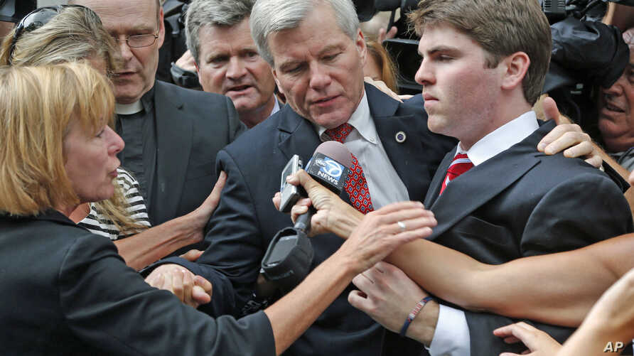 Former Virginia Gov. Bob McDonnell, center, is mobbed by media as he gets into a car with his son, Bobby, right, after he and his wife, Maureen, were convicted on multiple counts of corruption at Federal Court in Richmond, Va., Sept. 4, 2014.