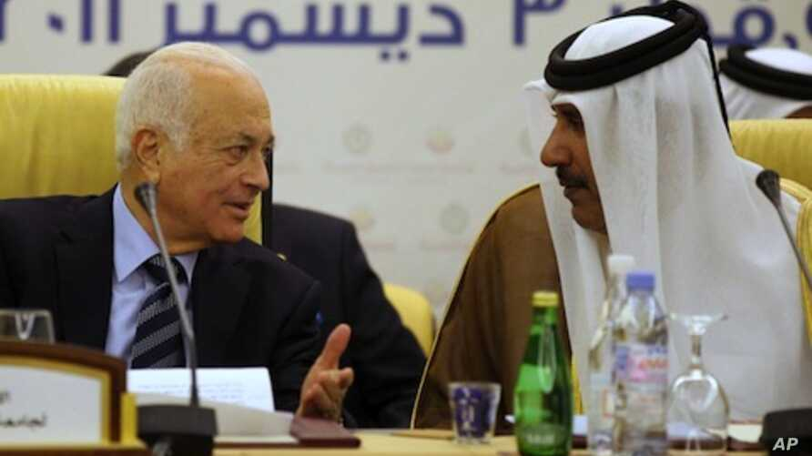 Qatar's Prime Minister and Foreign Minister Hamad bin Jassim bin Jabr Al-Thani (R) speaks with Arab League Secretary General Nabil al-Arabi during a meeting of the Committee of Arab Coordination in Doha, December 3, 2011.