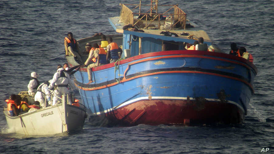 Photo released by the Italian Navy June 30, 2014 shows motor boats from the Italian frigate Grecale approaching a boat overcrowded with migrants in the Mediterranean Sea.