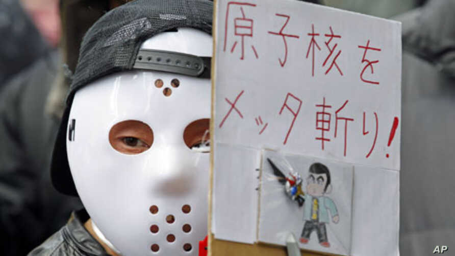 A protester wearing a mask holds a sign at a rally, in front of the headquarters of Tokyo Electric Power Company [TEPCO], aimed at criticizing TEPCO and demanding the abolition of nuclear power, in Tokyo,  March 3, 2012.