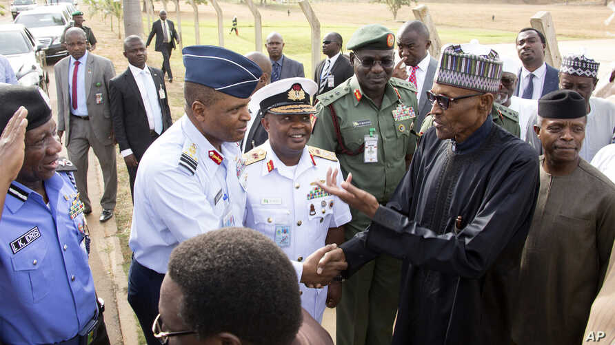In this photo released by the Nigeria State House, Nigeria President Muhammadu Buhari, second right, is welcomed by Nigeria Service Chiefs, on arrival from his medical vacation in Abuja, Nigeria, March 10, 2017.