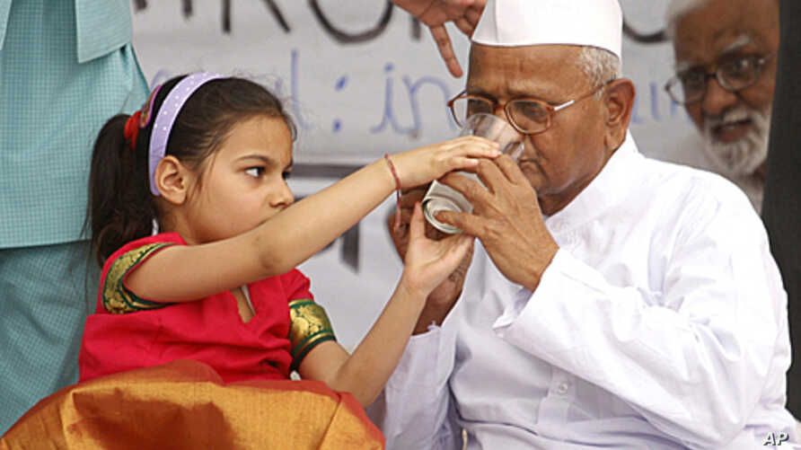 A girl offers lemon juice to social activist Anna Hazare after he called off his hunger strike during a campaign against corruption in New Delhi, April 9, 2011.