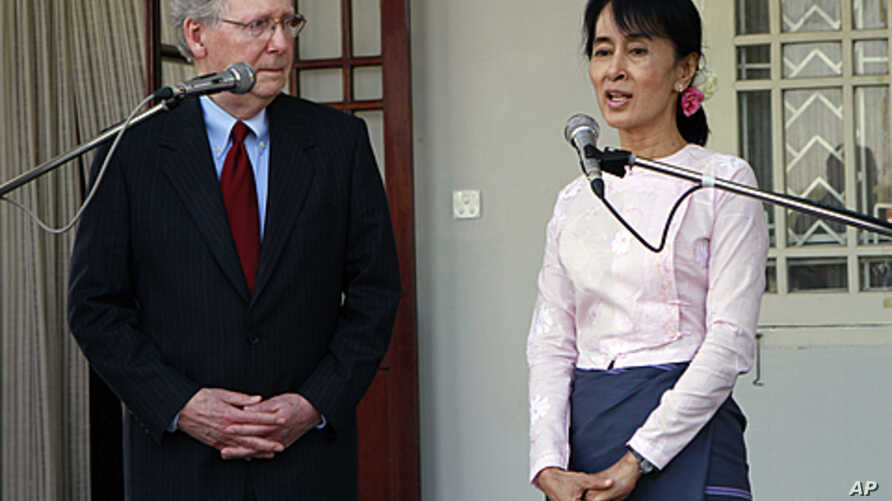 U.S. Senator Mitch McConnell, left, listens to Burmese pro-democracy leader Aung San Suu Kyi talk to journalists during a press conference after their meeting at her home in Rangoon, January 16, 2012.