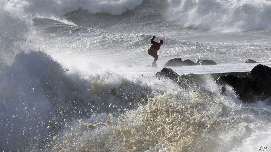 A man tries to keep his balance as waves hit the seawall at the beach in Anglet, southwestern France, Jan.13, 2017.