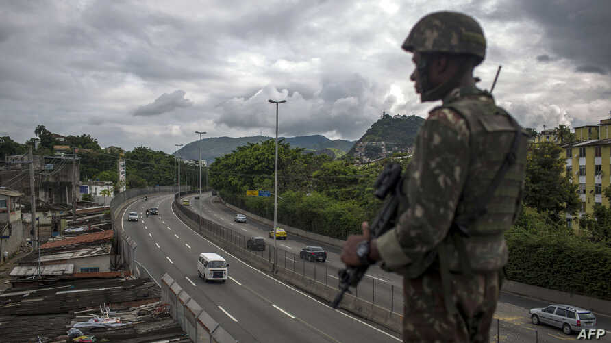 "A Brazilian army soldier stands guard over the ""Linha Amarela"" (yellow line) road during a joint operation at ""Cidade de Deus"" (City of God) favela in Rio de Janeiro, Feb. 07, 2018."