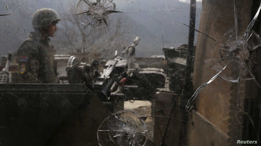 An Afghan National Army (ANA) soldier is seen through damaged glass as he keeps watch at the Forward Base in Nari district near the army outpost in Kunar province, February 24, 2014. The Afghan Taliban killed 21 soldiers in the assault on Sunday in t