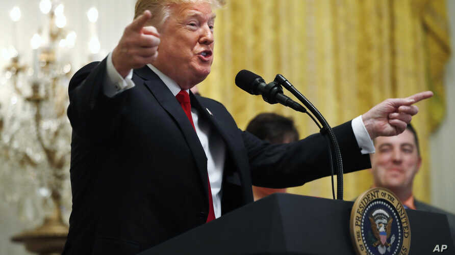 FILE - President Donald Trump gestures as he speaks about taxes, June 29, 2018, during an event in the East Room of the White House in Washington.