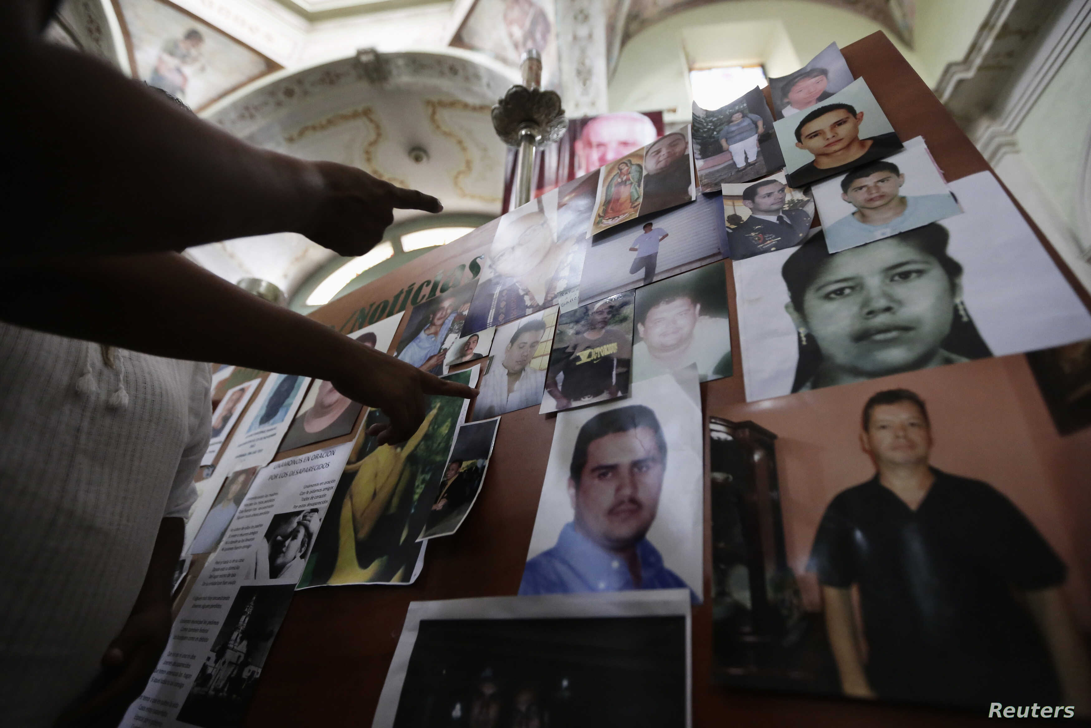 A parishioner points at photographs of missing persons during a mass to commemorate the International Day of the Victims of Enforced Disappearances in San Francisco de Asis church in Tala, in Jalisco state, Mexico, Aug. 31, 2014.