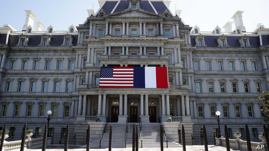 The U.S. and French flags are displayed on the Eisenhower Executive Office Building, April 20, 2018, in Washington.