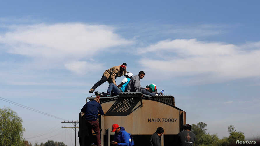 Central American migrants, moving in a caravan through Mexico, travel on a wagon of a freight train after stopping it on the rail line, in Michoacan state, Mexico, April 17, 2018.
