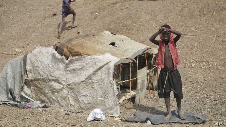 FILE - A young boy stands outside his small shelter in the United Nations protection of civilians site in Bentiu, South Sudan, Dec. 9, 2018.