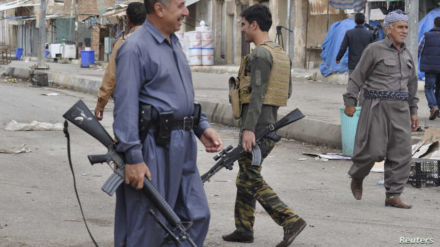 Kurdish fighters guard in the street in the Iraqi town of Qara Tappa north of Baghdad, October 21, 2014.