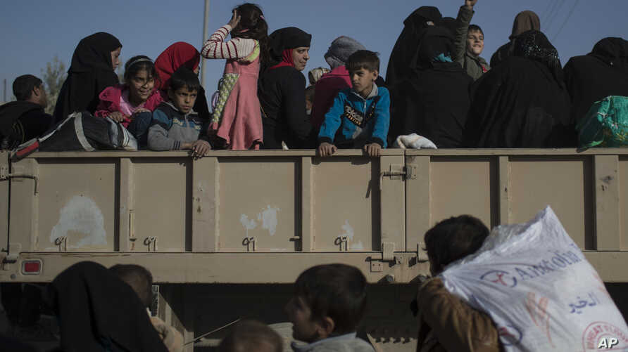 FILE - Women and children displaced by fighting between Iraqi forces and Islamic state militants stand inside a truck as they wait to be taken out of Mosul, Iraq, Nov. 18, 2016.