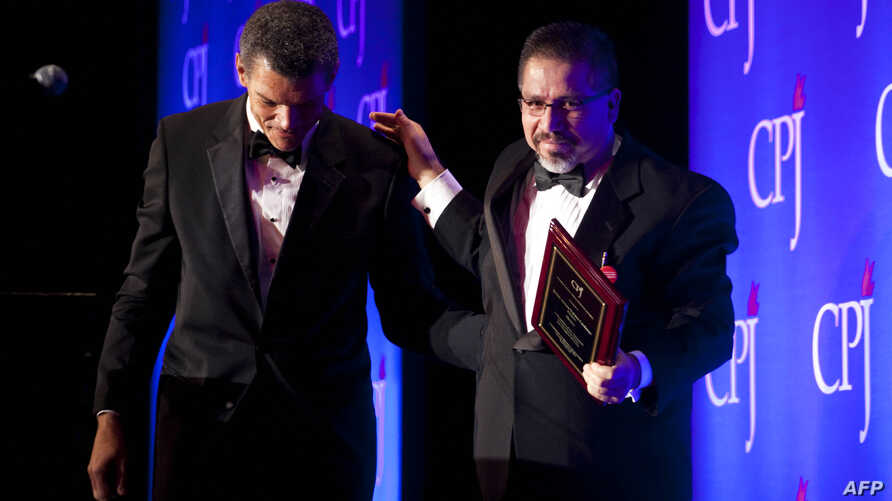 FILE - Mexican journalist Javier Valdez Cardenas (R) walks off stage after accepting the 2011 International Press Freedom award in New York, Nov. 22, 2011