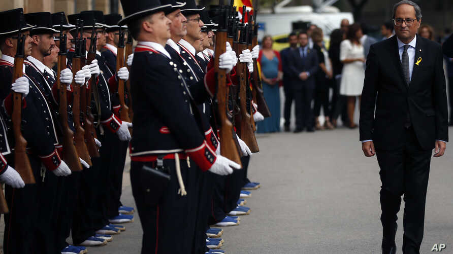 Regional Catalan President Quim Torra (Rr) walks next to the Catalan regional police 'Mossos D'Esquadra' honor guards the day ahead of the Catalan National Day in Barcelona, Spain, Sept. 10, 2018.