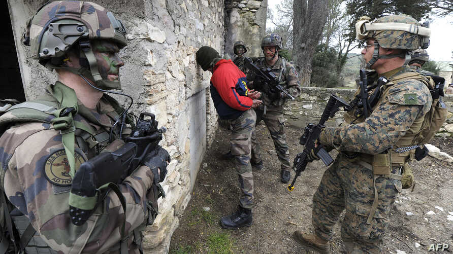 "FILE - Soldiers of the Special Purpose Marine Air-Ground Task Force (SPMAGTF) and soldiers of the French 21st Marine Infantry Regiment arrest the acting terrorist ""Geronimo"" as they take part in a Franco-American military exercise called ""Garrigues F"