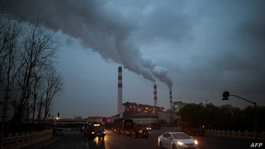 FILE - Cars pass the Shanghai Waigaoqiao Power Generator Company coal power plant in Shanghai, March 22, 2016.