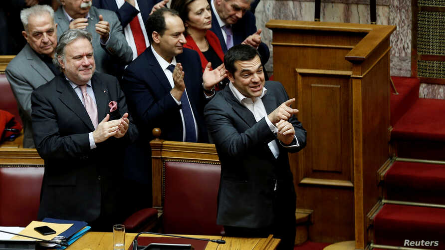 Greek Prime Minister Alexis Tsipras and members of his government applaud after a vote on an accord between Greece and Macedonia changing the former Yugoslav republic's name in Athens, Greece, January 25, 2019.