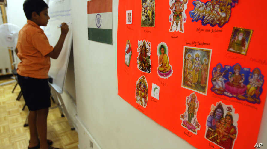 **ADVANCE FOR TUESDAY, SEPT. 5** A poster displaying the religions of India and the Indian flag hang on the wall as Arvind Venkatramana, 9, works on the board during class at the India Heritage Camp, Thursday, Aug. 17, 2006 in New York. Hindus in the
