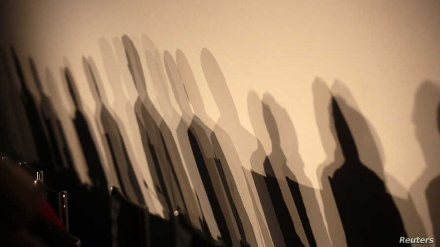 "FILE - Shadows of members of a panel are seen on a wall before a meeting about the ""right to be forgotten"" in Madrid, Sept. 9, 2014."