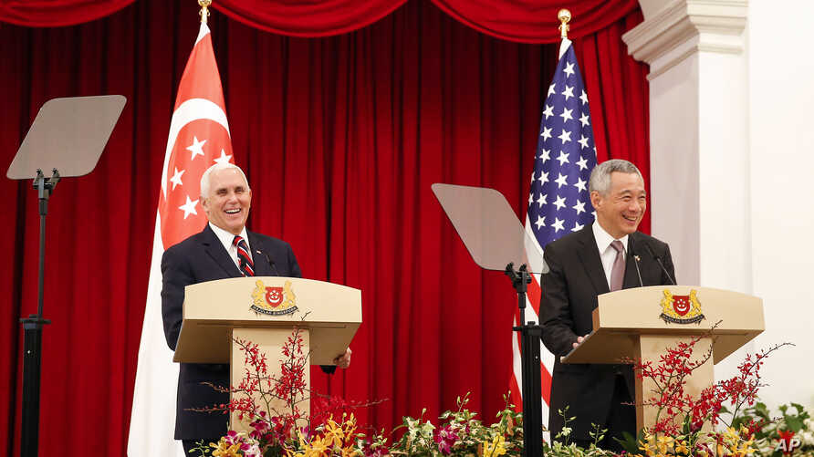 U.S. Vice President Mike Pence, left, and Singaporean Prime Minister Lee Hsien Loong speak at a joint press conference at the Istana or Presidential Palace in Singapore, Friday, Nov. 16, 2018.