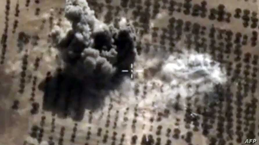 FILE - An image taken from video footage made available on the Russian Defense Ministry's official website purports to show an explosion after airstrikes carried out by Russian air force on what Moscow says was an Islamic State facility in the Syrian