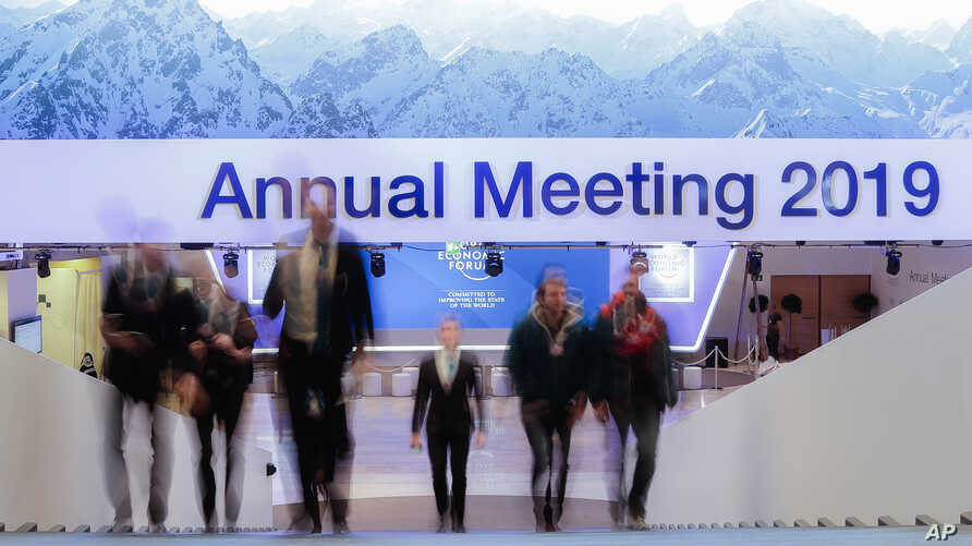 People walk up stairs at the congress center where the annual meeting of the World Economic Forum 2019, WEF, take place in Davos, Jan. 20, 2019.