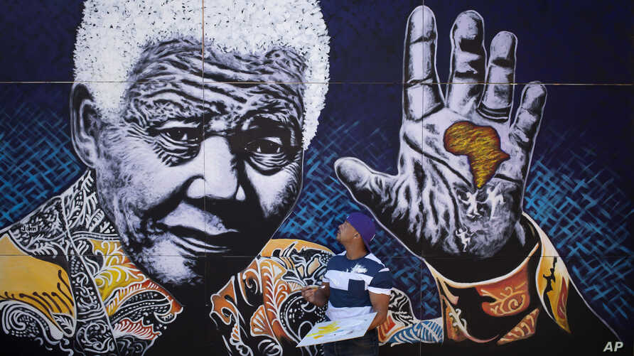 South African artist John Adams works on a giant acrylic-on-canvas painting of Nelson Mandela in the driveway of his house in a suburb of Johannesburg, South Africa, Monday, July 15, 2013.