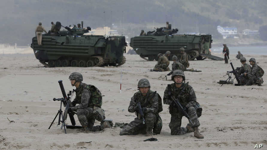South Korean Marines and U.S. Marines from 3rd Marine Expeditionary Force based Okinawa, Japan, take positions near Amphibious Assault Vehicle (AAV) during the U.S.-South Korea joint military exercises called Ssangyong 2013 as part of their two-month