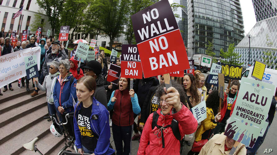 FILE - Protesters wave signs and chant during a demonstration against President Donald Trump's travel ban, outside a federal courthouse in Seattle, Washington, May 15, 2017.