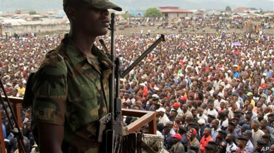 A soldier from the M23 rebel group looks on as thousands of Congolese people listen during an M23 rally, in Goma, eastern Congo, Nov. 21, 2012