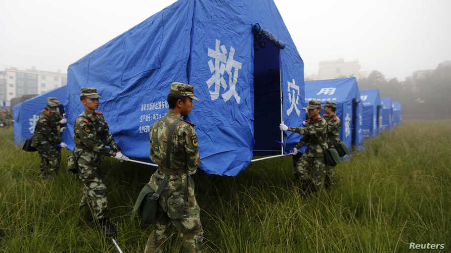Paramilitary policemen set up a relief tent in Yongping township after an earthquake hit Jinggu county, Yunnan province, October 8, 2014.