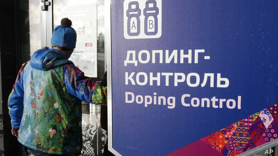 """A man walks past a sign reading """"Doping Control"""" in Russian at a 2014 Sochi Winter Olympics site in Krasnaya Polyana, Russia. Feb. 21, 2014. Moscow has been under fire for months over allegations of state-run doping."""