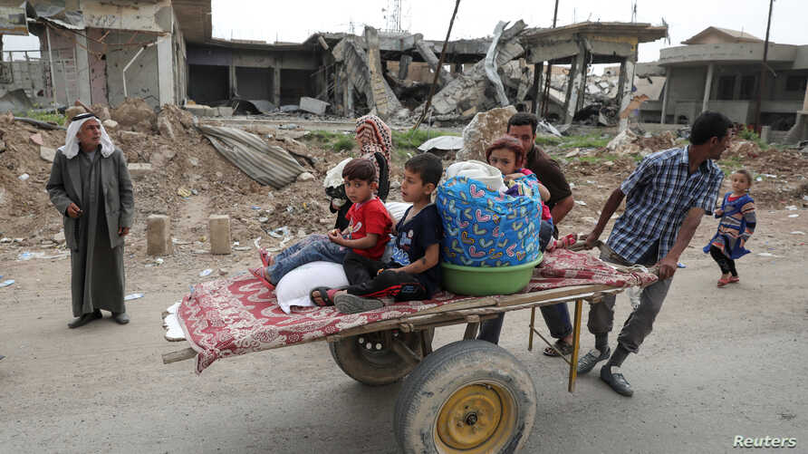A displaced Iraqi family is transported on a cart as the battle between the Iraqi Counter Terrorism Service and Islamic State militants continues nearby, in western Mosul, April 23, 2017.
