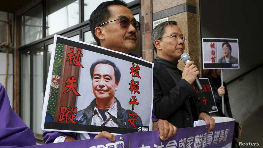 Pro-democracy Civic Party protesters carry portraits of missing booksellers Lee Bo, left, and Gui Minhai outside the Chinese Liaison Office in Hong Kong, Jan. 19, 2016.
