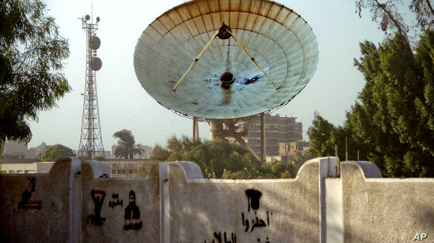 A satellite dish stands damaged after an attack on Egypt's main satellite station in the Maadi district of Cairo October 7, 2013.