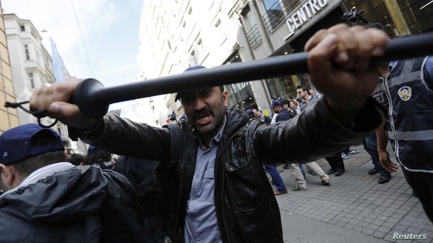 FILE - A plainclothes police officer reacts against journalists during a protest by anti-government demonstrators in central Istanbul, May 31, 2014.