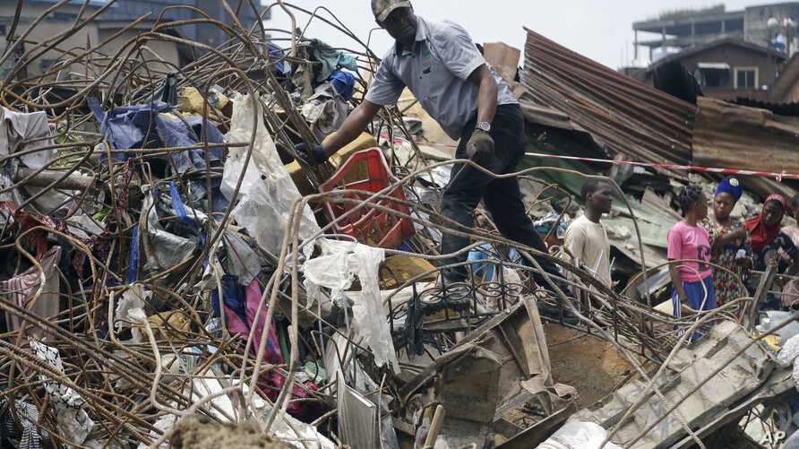 Government officials from Standard Organisation of Nigeria examine materials used in constructing the building that collapsed in Lagos, Nigeria, March 14, 2019.