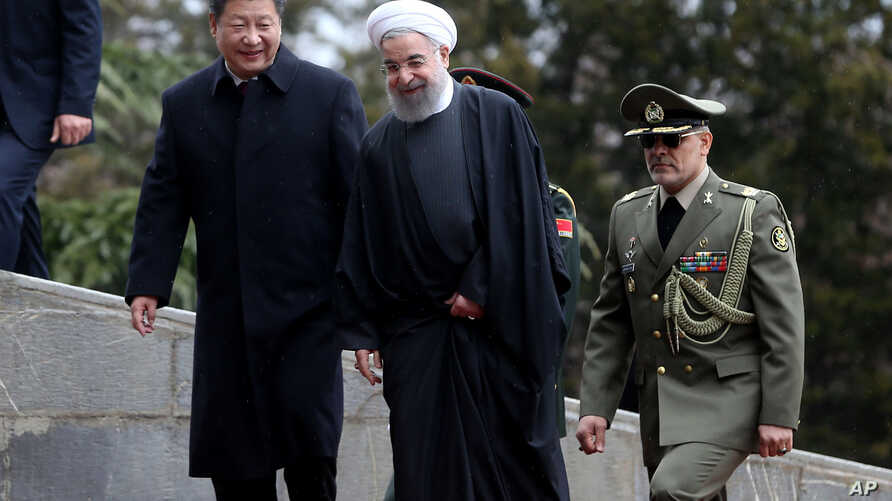 Chinese President Xi Jinping, left, is welcomed by Iranian President Hassan Rouhani during his official arrival ceremony at the Saadabad Palace in Tehran, Iran, Jan. 23, 2016.