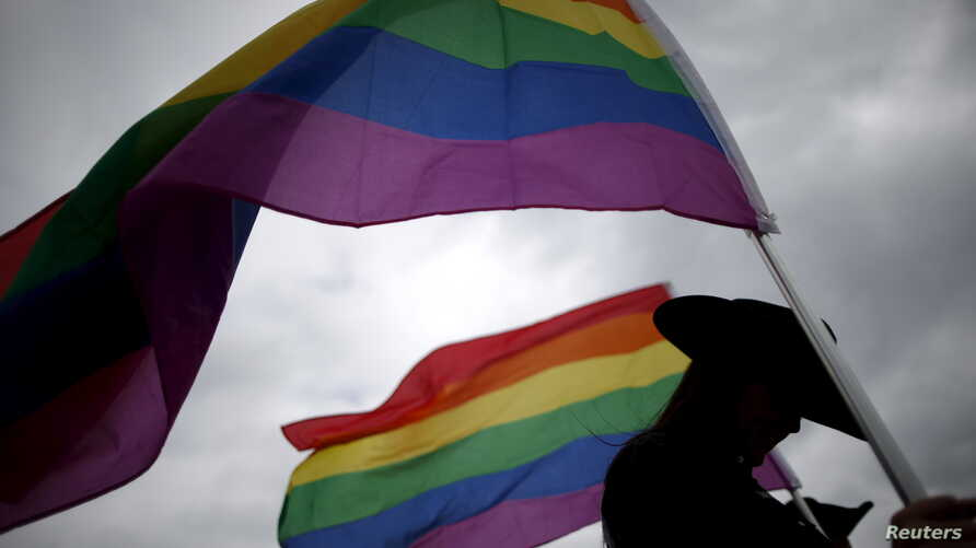 FILE -A woman holds rainbow flags for the grand entry at the International Gay Rodeo Association's Rodeo In the Rock in Little Rock, Arkansas, United States, April 26, 2015.