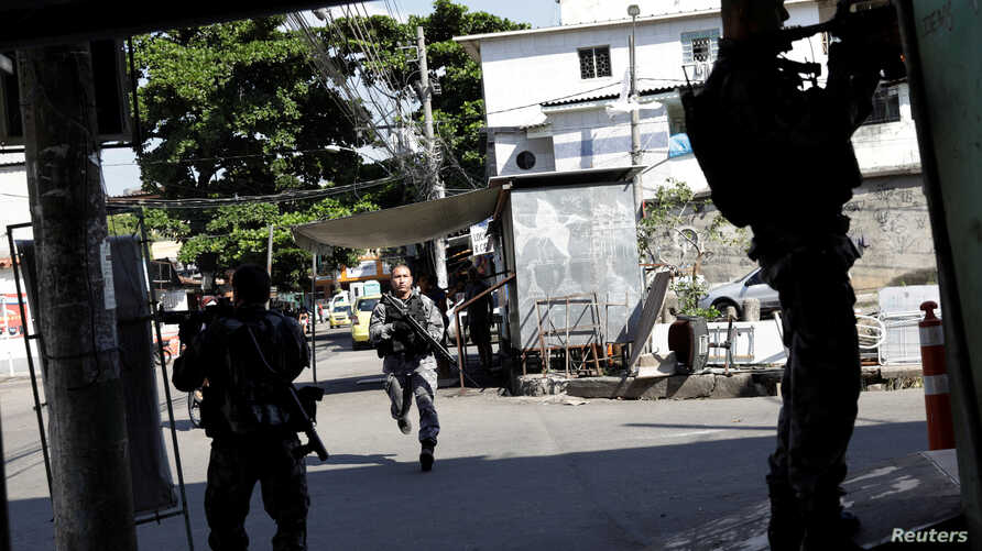 Policemen take up positions during an operation in Alemao slums complex, after violent clashes between policemen and drug dealers in Rio de Janeiro, Brazil May 4, 2017.